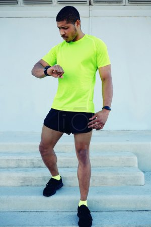 male runner looking at his watch