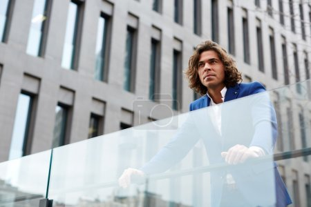 Photo for Portrait of handsome confident man leaning on glassy fence while standing against big office building in urban setting, attractive well dressed man looking away confident and concentrated - Royalty Free Image