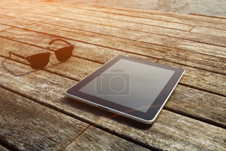 Sunglasses and digital tablet on wooden jetty
