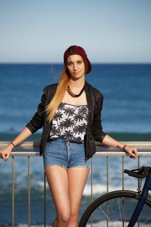 Photo pour Verticale de moitié longueur de fille de hipster élégante restant avec son vélo fixe de train de sport sur la plage, jeune femme appréciant l'extérieur beau d'après-midi avec la mer bleue sur le fond, promenade au jour ensoleillé - image libre de droit