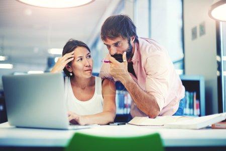 Photo pour Deux employés de bureau discutant dans un bureau intérieur, de jeunes collègues d'affaires discutant du travail sur un ordinateur portable dans un espace de co-travail, des gens d'affaires d'entreprise regardant un ordinateur portable avoir une conversation - image libre de droit