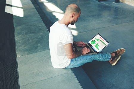 Photo pour Étudiant beau étudiant sur son ordinateur portable tout en étant assis dans le hall de l'université, pigiste masculin occupé à travailler sur netbook tout en tapant du texte sur le clavier, jeune homme faisant de l'argent en ligne, e-business - image libre de droit