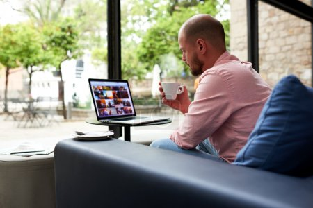 Photo pour L'homme beau travaillent sur l'ordinateur portatif se reposant dans le café moderne avec de grandes fenêtres, jeune homme d'affaires retenant la tasse de thé se reposant sur le sofa, étudiant masculin avec le cahier ouvert dans la bibliothèque d'université - image libre de droit