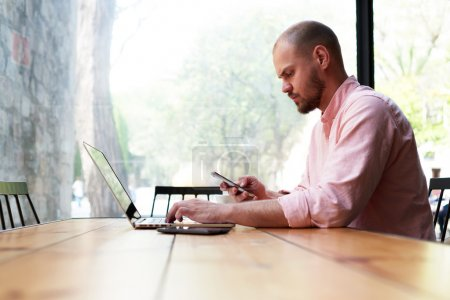 Photo for Modern business man using smart phone and laptop computer in light loft interior, young hipster busy using smart phone at office desk, male student texting message on phone at wooden coffee shop table - Royalty Free Image