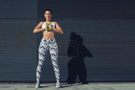 Photo pour Athlétique femelle tenant haltères haltères poids avec ses mains ensemble, jeune femme en tenue sportive entraînement bicep boucles à l'extérieur avec copie espace arrière-plan pour message texte par côté, image filtrée - image libre de droit
