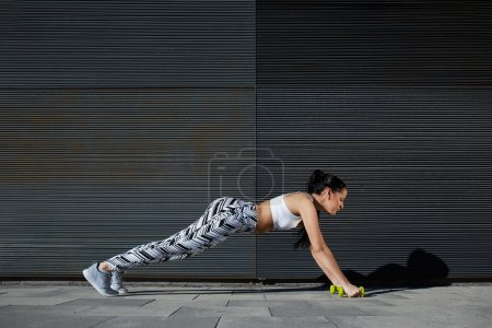woman doing press ups with dumbbells