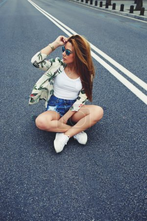 hipster girl sitting  in the middle of asphalt road