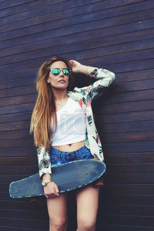 Foto de Retrato de hipster femenino vestido casualmente sosteniendo monopatín mientras ella de pie sobre fondo de pared de madera en verano, joven mujer de moda en gafas de sol posando con su longboard disfrutando de un buen día - Imagen libre de derechos