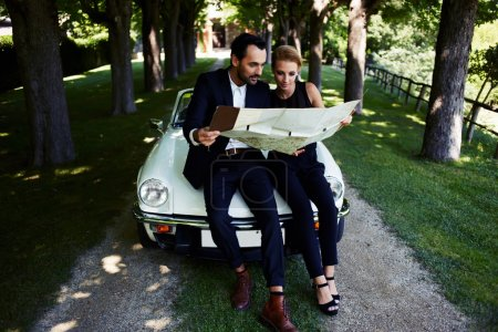 Beautiful couple with map near car