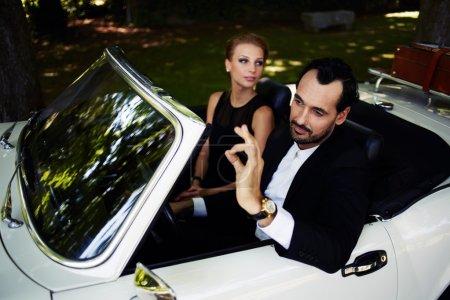 Photo pour Richement habillé couple riche et célèbre assis à l'intérieur voiture de luxe cabriolet, homme à succès assis derrière le volant convertible avec son geste ok main, homme heureux et femme profiter de la vie - image libre de droit