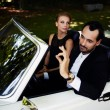 Richly dressed wealthy and famous couple sitting i...