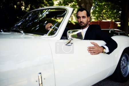 wealthy businessman in luxury car