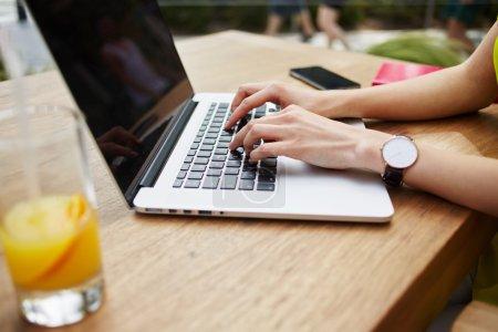 woman's hands keyboarding on laptop