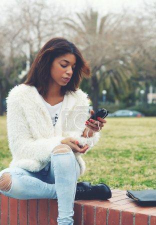 Photo pour Élégant hipster girl tenant le téléphone intelligent tout en étant assis dans le parc à l'extérieur, femme afro-américaine attrayante utilisant un téléphone portable tout en bavardant ou en lisant un message texte, jeune adolescent tenant le téléphone mobile - image libre de droit
