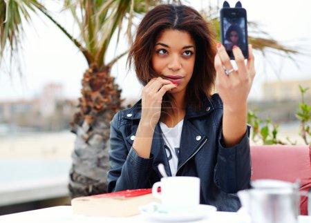 Photo pour Touriste féminine utilisant un appareil photo de téléphone mobile pour prendre une photo de soi pendant les vacances à Barcelone, femme afro-américaine élégant prenant autoportrait avec smartphone, se sentant bien et heureux - image libre de droit