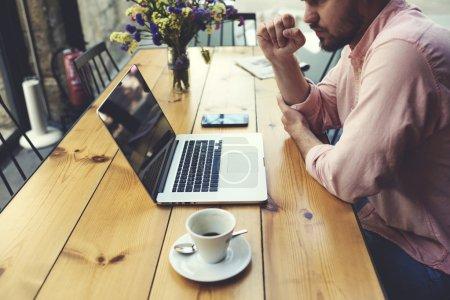 Photo pour Homme pigiste se connectant au sans fil via ordinateur portable, homme d'affaires réfléchi travailler sur ordinateur portable tout en étant assis à la table en bois dans l'intérieur du café moderne, texte de lecture étudiant ou livre dans le café - image libre de droit