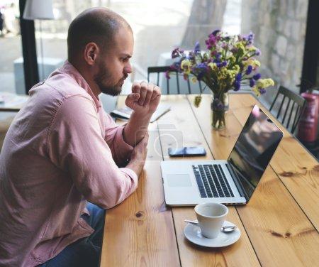 Photo pour Un homme d'affaires réfléchi travaille sur un ordinateur portable assis à une table en bois dans un café moderne, un étudiant lisant un texte ou un livre dans un café, un pigiste masculin se connectant au sans fil via un ordinateur portable - image libre de droit