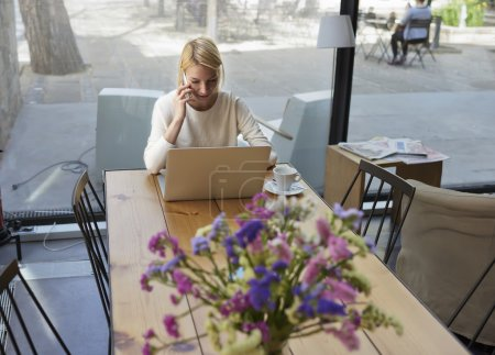Photo pour Jeune femme d'affaires assis devant ordinateur portable ouvert et parler sur smartphone, personne féminine utilisant net-book pendant le petit déjeuner du matin dans un café moderne, pigiste travaillant sur la distance dans le café - image libre de droit