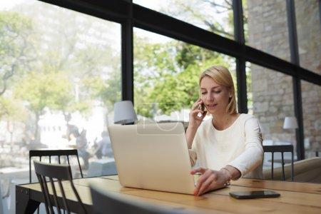 Photo pour Femme confiante parlant sur téléphone portable avec tout en étant assis à la table en bois avec ordinateur portable ouvert, jeune étudiant ou femme d'affaires au travail pause avec net-book dans l'intérieur du café moderne - image libre de droit