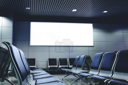 Photo for Blank billboard with clean space for publicity content or text message, advertising mock up in interior, public commercial board in waiting of airport hall with empty chairs, template banner indoors - Royalty Free Image