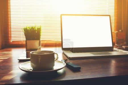 Photo pour Accueil bureau indépendant avec ordinateur portable ouvert, tasse de café, tablette numérique et plante verte couché sur la table, net-book de personne d'affaires avec écran blanc pour le contenu de l'information ou message texte - image libre de droit