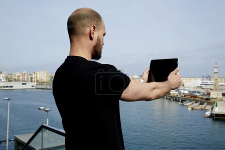 Photo for Attractive tourist with digital tablet camera taking picture of beautiful city from viewpoint, young handsome man photographing marina port city with touch pad,male enjoying vacation journey in summer - Royalty Free Image