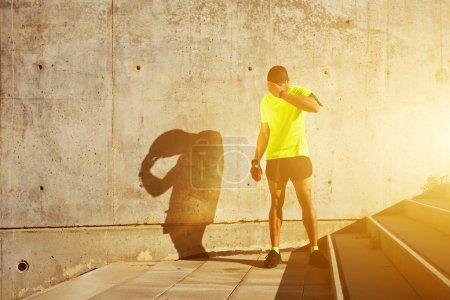 Photo pour Jeune homme musclé avec brassard de course sur le bras se reposant après le jogging tout en se tenant contre un mur de ciment avec espace de copie pour votre message texte ou contenu, sportif épuisé prendre une pause - image libre de droit