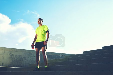 Photo for Portrait of a runner man with armband on the arm rest after jogging while standing on ladder against the sky background with copy space area for your text message information,sportsman taking a break - Royalty Free Image