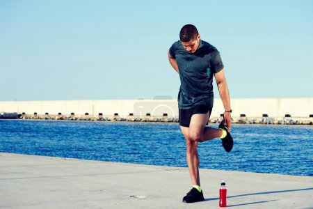 Male runner stretching legs