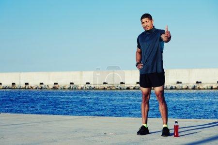 Handsome male runner shows okay
