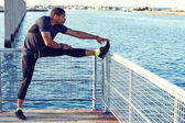 Male jogger doing stretching exercise