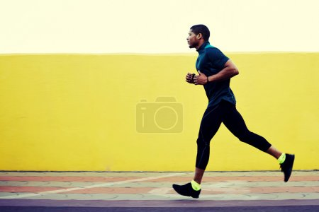 Photo for Full length portrait of afro american runner in tracksuit jogging fast against yellow background with copy space area for text message or advertising content, athletic build man working out outdoors - Royalty Free Image