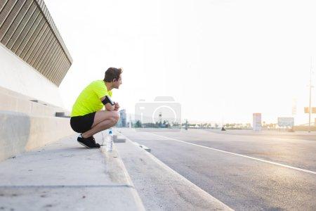 Photo pour Jeune sportif avec brassard bénéficiant en main belle matinée ensoleillée, tout en se préparant pour le jogging quotidien - image libre de droit