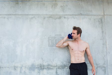 male athlete with bare-chested holding shirt