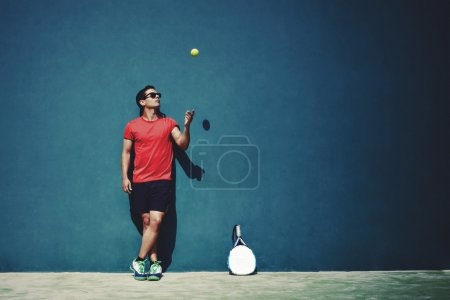 Young sportsman tossing  tennis ball