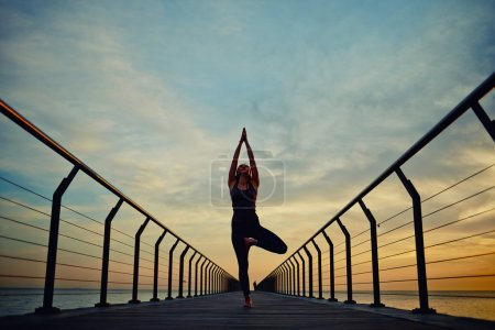 Photo pour Silhouette of young woman with beautiful figure engage yoga meditation at summer sunrise while standing on the pier with arms up - image libre de droit
