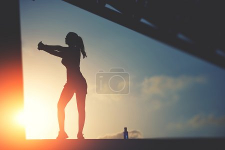 Photo for Half length portrait of sporty woman doing workout on sunset sky background in urban setting, silhouette of athletic female jogger against the sunset sky doing workout - Royalty Free Image