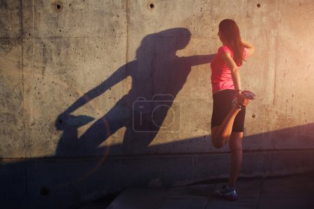 Photo for Half length portrait of female runner with beautiful figure doing stretching exercise before began her run, athletic woman warming up outdoors against  concrete wall background with copy space area for your text message or advertising content - Royalty Free Image