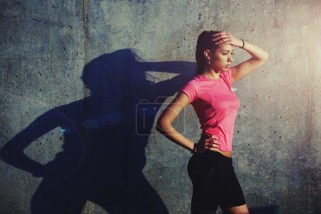 Photo pour Verticale de demi-longueur de jeune femme en forme avec la belle figure ayant le repos après l'entraînement à l'extérieur le soir, coureur féminin prenant la coupure après la course tout en restant contre le fond concret de mur avec la zone de rythme de copie pour votre contenu de massage de texte - image libre de droit