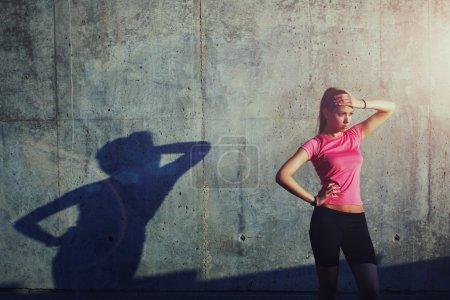 Photo pour Charmante femme tenant la main au front tout en se tenant contre un mur gris avec sa propre ombre - image libre de droit