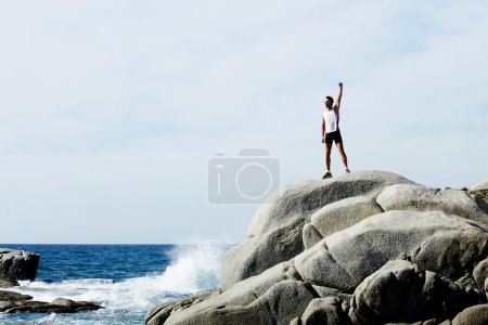 male runner standing on the rock