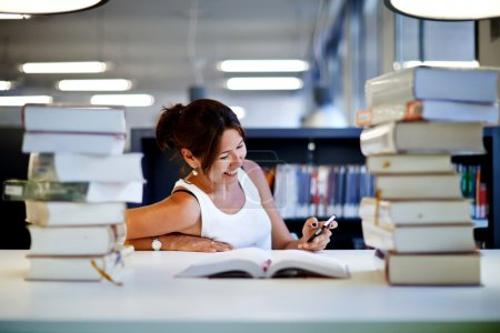 Young lady using smartphone in a library