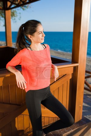 Photo for Portrait of lovely young woman posing for the camera while enjoying the fresh air in summer sunny day, attractive female runner looking to the sea scenery while taking break after morning jog outdoors - Royalty Free Image