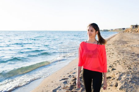 Photo pour Young beautiful female runner walking along the beach with copy space for your text message or advertising content, attractive woman enjoying sunny day after workout training at seashore in summer - image libre de droit