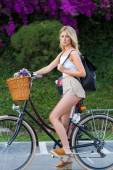 Woman riding on bicycle in park with flowers