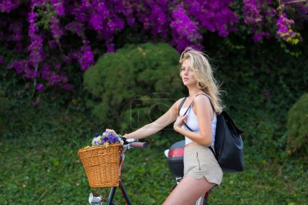 Female riding on bicycle in park with flowers