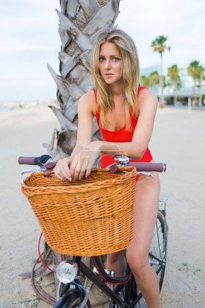 Photo pour Jeune femme attirante rectifiée dans les maillots de bain sexy se reposant sur la plage tout en s'asseyant sur le vélo classique - image libre de droit