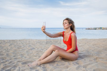 Woman in red swimsuit doing self portrait