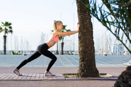 Photo for Full length portrait of a young athletic female with perfect figure dressed in sportswear do physical exercises in the street,healthy fit woman with perfect body stretching outdoors in summer day - Royalty Free Image