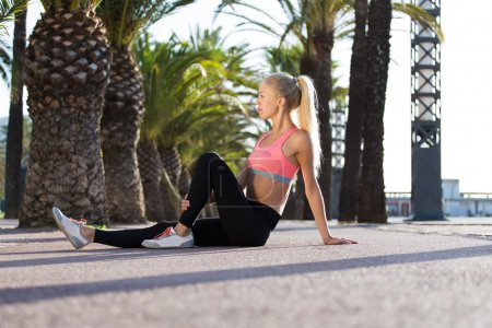 Fit woman relaxing after physical exercises